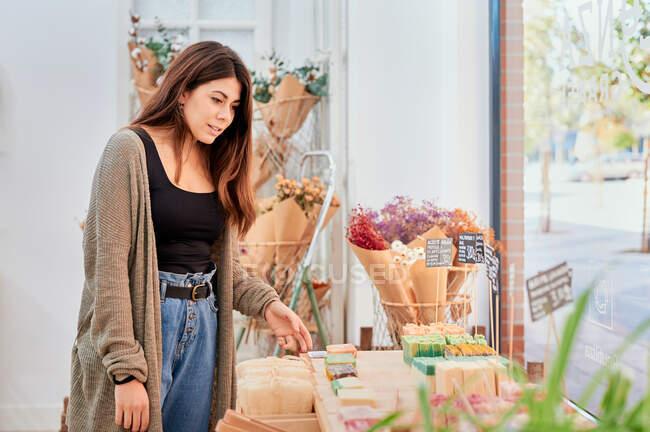 Compras do comprador fêmea na loja com vários sabão orgânico caseiro e produtos — Fotografia de Stock
