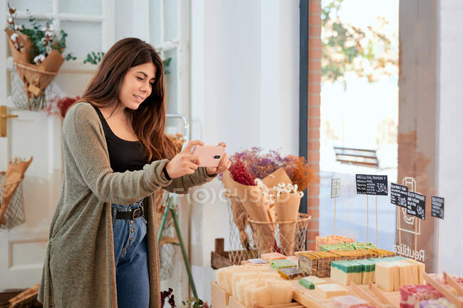 Smiling female taking photo of organic soap selling in bulk store with eco friendly products — Stock Photo