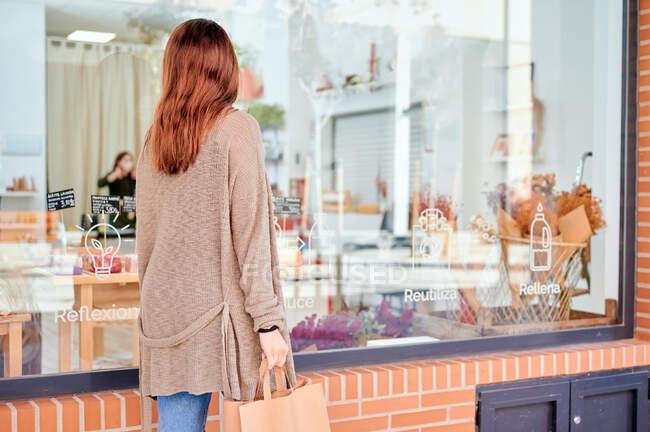 Visão traseira da fêmea irreconhecível com saco de compras andando pela vitrine da loja vendendo zero resíduos de mercadorias — Fotografia de Stock