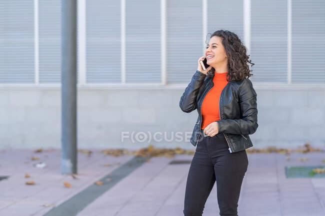 Jolie jolie femme en vêtements décontractés et veste en cuir ayant la conversation via téléphone mobile et regardant loin avec le sourire des dents tout en se tenant dans la rue — Photo de stock