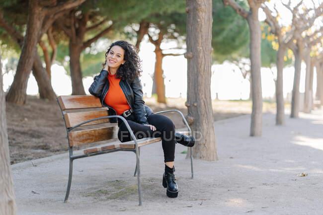 Pieno corpo attraente contenuto bruna in abbigliamento casual e giacca di pelle nera toccando teneramente il collo e guardando la fotocamera mentre si siede sulla panchina in un parco verde soleggiato — Foto stock