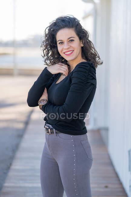 Feliz joven hembra en ropa casual mirando a la cámara con una sonrisa dentada y de pie con los brazos cruzados en la calle - foto de stock