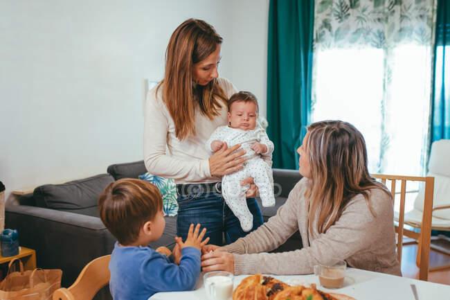 Gai homosexuel femme avec petit bébé debout près de la table avec petite amie et fils tout en prenant le repas — Photo de stock