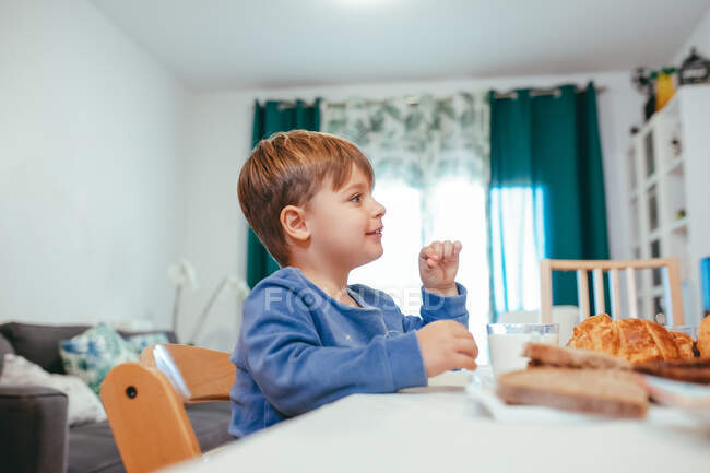 Side view of small smiling child sitting on chair at table with milk and baked goods at home — Stock Photo