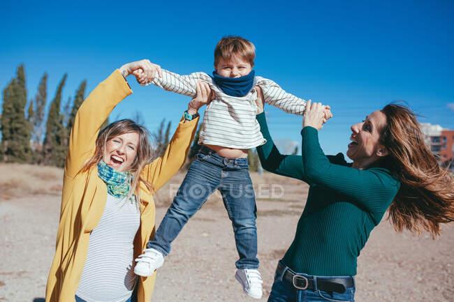 Радісна молода лесбійська пара, одягнена в повсякденний одяг, піднімає чарівного маленького сина за руки, проводячи час разом у сонячній природі. — стокове фото