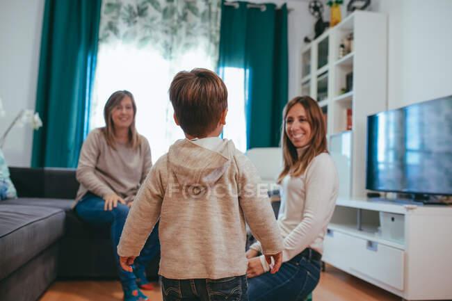 Sorrindo jovem casal lésbico brincando com crianças adoráveis enquanto passavam tempo livre juntos na sala de estar moderna — Fotografia de Stock