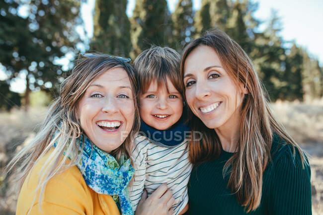 Alegre lesbiana pareja abrazando lindo pequeño hijo y mirando a cámara con amistoso sonrisas mientras pasar soleado día en pacífica naturaleza - foto de stock