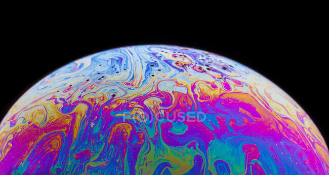 Panoramic view of closeup bubble textured backdrop representing colorful planet with wavy lines on round shaped surface on black background — Stock Photo