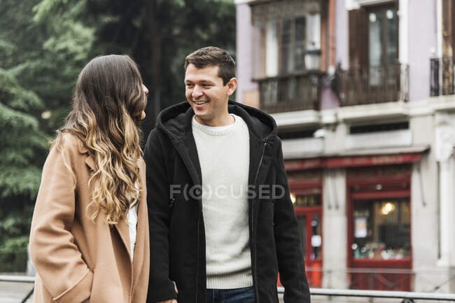 Alegre pareja joven con ropa de abrigo tomados de la mano y mirándose con sonrisas mientras caminan juntos en la acera de asfalto en la ciudad moderna - foto de stock