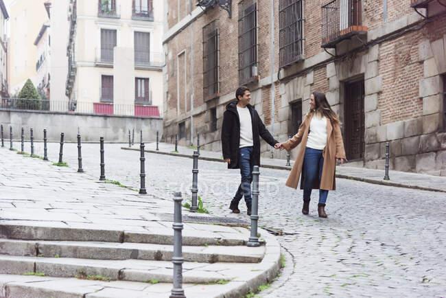 Pareja joven alegre de cuerpo entero que lleva ropa de abrigo cogida de la mano y se mira con sonrisas mientras caminan juntos en la acera de asfalto en la ciudad moderna - foto de stock