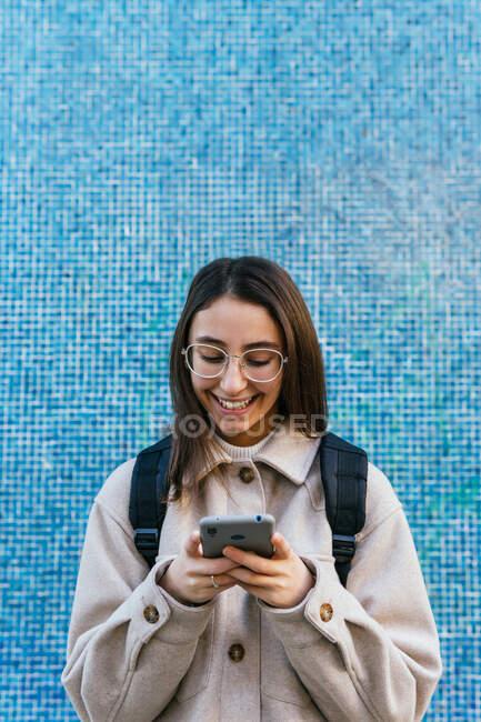 Урожай привлекательный улыбающийся студентка в теплой одежде с рюкзаком с помощью современного мобильного телефона на тротуаре на улице — стоковое фото