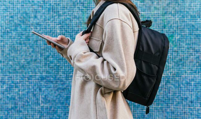Невпізнавана студентка в повсякденному одязі з рюкзаком, що стоїть навпроти синьої стіни з покришками. — стокове фото