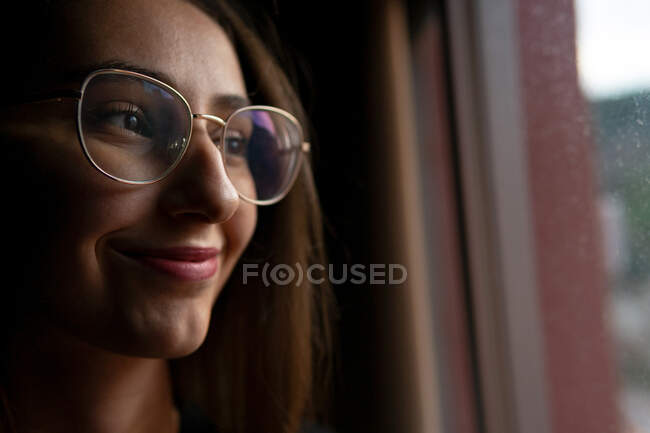 Crop positive young female with dark hair wearing eyeglasses standing in dark room and looking out window with smile — Stock Photo
