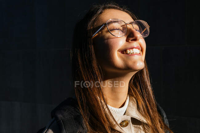 Delighted young female with dark hair wearing stylish eyeglasses standing with eyes closed and toothy smile while enjoying warm sunlight on street — Stock Photo