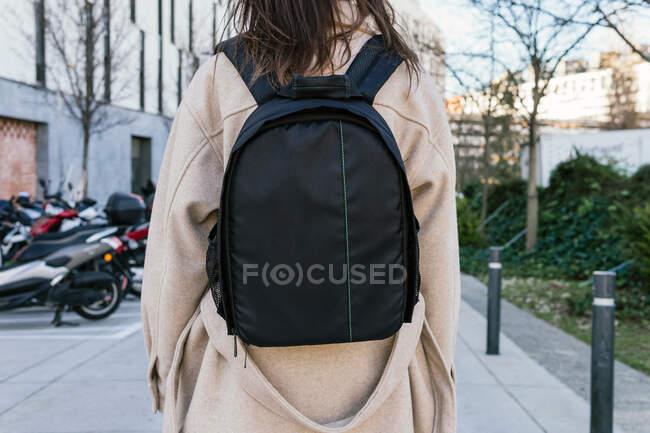 Vue de dos femelle méconnaissable en manteau chaud portant un sac à dos noir se promenant dans la rue urbaine — Photo de stock