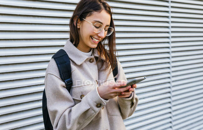 Радостная молодая женщина в теплой одежде и очках с рюкзаком просматривает современный мобильный телефон, стоя на тротуаре — стоковое фото