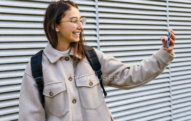 Cheerful young female in warm wear with backpack taking selfie on mobile phone while standing on sidewalk — Stock Photo