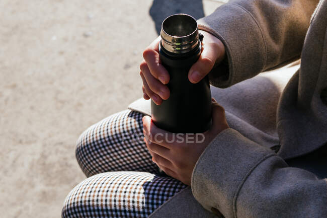 High angle crop female wearing warm clothes holding opened reusable water bottle on knees while sitting on bench on sunny autumn street — Stock Photo