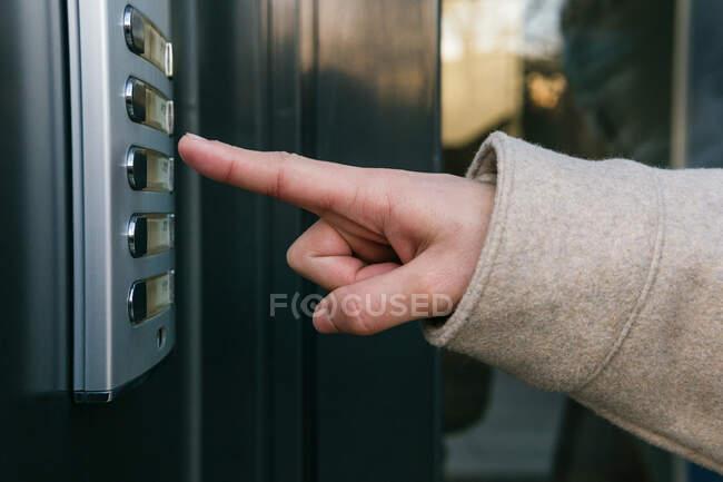 Копни анонімну жінку в теплому пальто, натискаючи кнопку входу, стоячи біля вхідних дверей в ясний осінній день — стокове фото