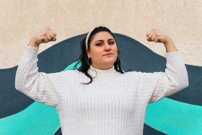 Молода сильна жінка в білому носовичку стоїть з піднятими руками і дивиться на фотоапарат на вулиці — стокове фото
