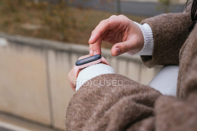 Side view of crop anonymous female in warm clothes using wearable bracelet in town in daylight — Stock Photo