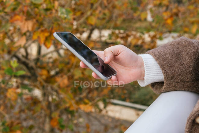 Ковзанка анонімної молодої пухнастої жінки в пальто серфінг інтернет на мобільному телефоні в місті — стокове фото
