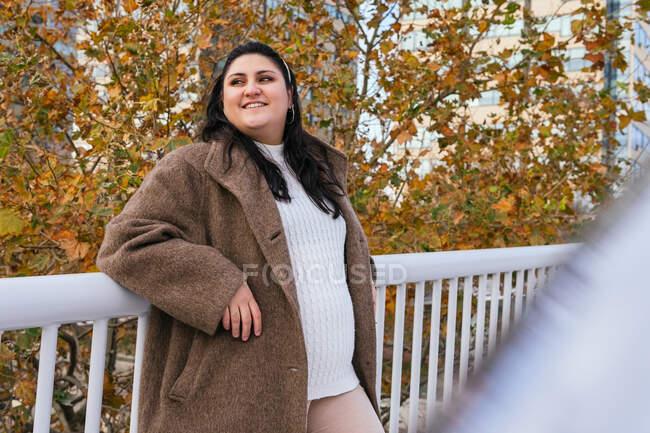 Jeune femme gaie plus la taille en manteau et pull tricoté regardant loin tout en s'appuyant sur la clôture contre les arbres brillants à l'automne — Photo de stock