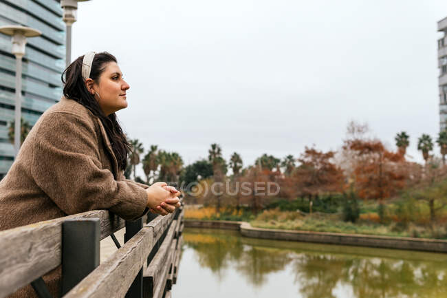 Side view of young plump female with clasped hands admiring water channel reflecting bright trees and looking away in town — Stock Photo