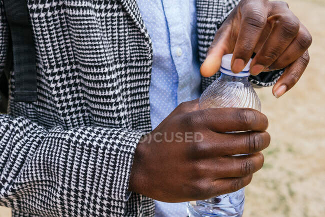 Crop unrecognizable ethnic male office worker in formal apparel opening plastic bottle cap in town — Stock Photo
