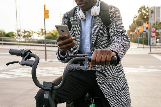 Crop of young black male office worker with headset chatting on cellphone while sitting on bike on urban pavement — Stock Photo