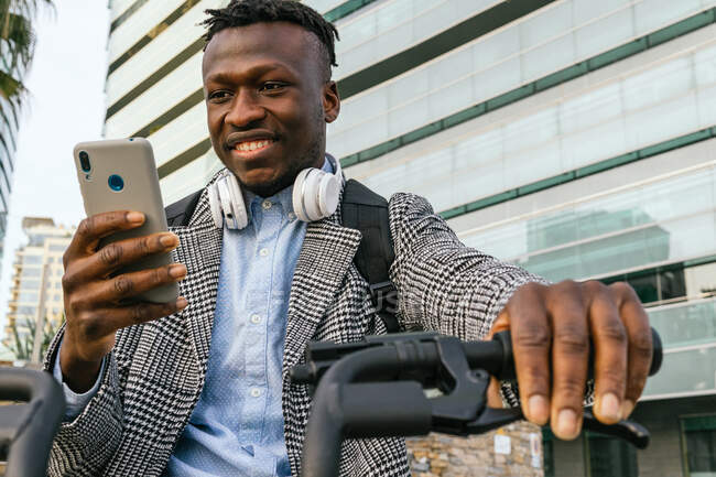 Crop glad African American male office employee with headset browsing internet on mobile phone while sitting on bike in city — Stock Photo