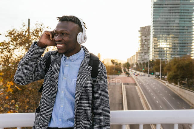 Young cheerful African American male office worker in formal wear listening to music in headphones while looking away in town — Stock Photo