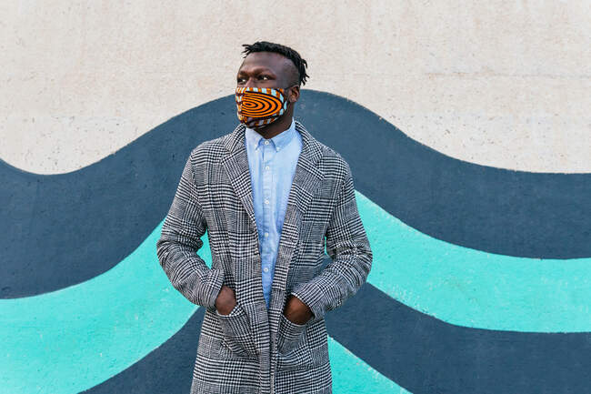 Unrecognizable thoughtful African American male executive in face mask standing with hands in pockets near bright wall and looking away in town — Stock Photo