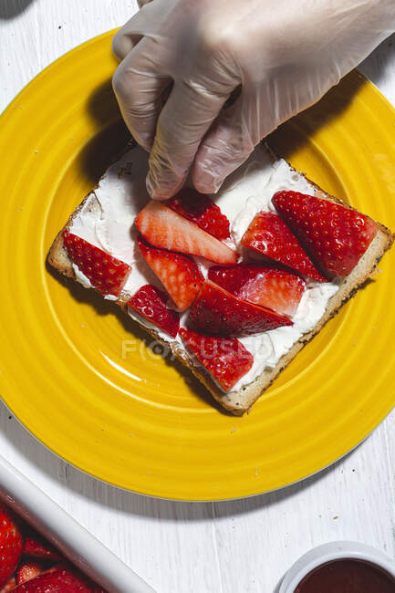 Top view crop anonymous chef in glove arranging cut strawberries on bread toast with spread cream cheese — Stock Photo
