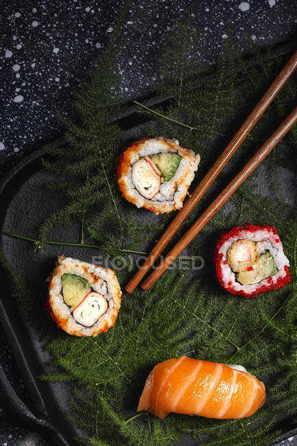 Top view composition of delicious fresh various sushi and bamboo chopsticks served on black platter on checkered cloth — Stock Photo