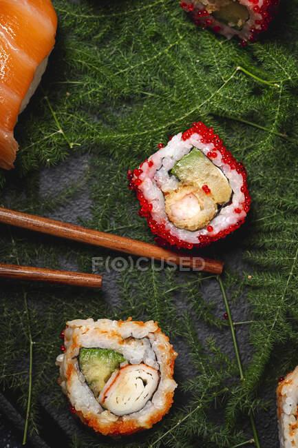 Leckeres frisch sortiertes Sushi auf grünen Pflanzenzweigen auf schwarzem Teller mit Sojasauce auf Marmortisch neben Essstäbchen — Stockfoto