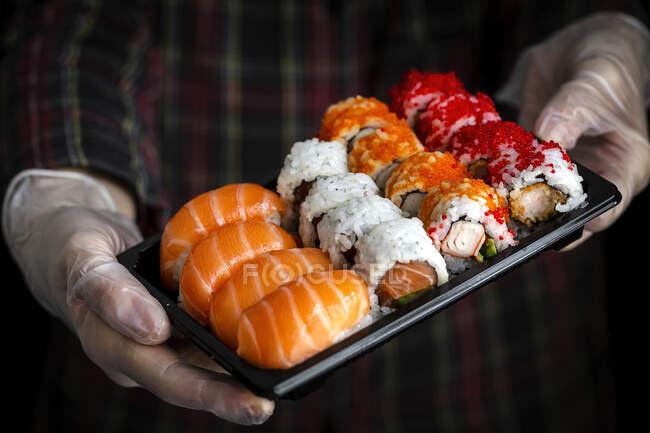 Ernte unkenntlich Koch in Handschuhen zeigt Platte mit einer Reihe von schmackhaften sortierten Sushi in dunklen Raum — Stockfoto