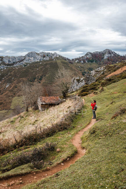 Side view faceless traveler standing on rural path on grassy slope in spacious mountainous terrain on overcast day in Asturias Spain — Stock Photo