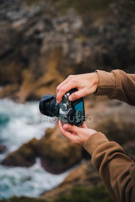 Ritaglia anonimo fotografo maschio scattare foto su macchina fotografica professionale di acqua di mare schiumosa lavaggio ruvida scogliere rocciose — Foto stock