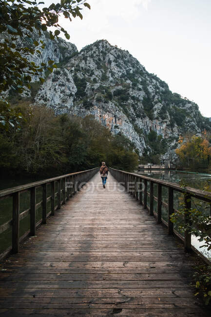 Туристическая прогулка по узкой деревянной тропинке над спокойным озером в сторону сурового горного хребта в Астурии — стоковое фото
