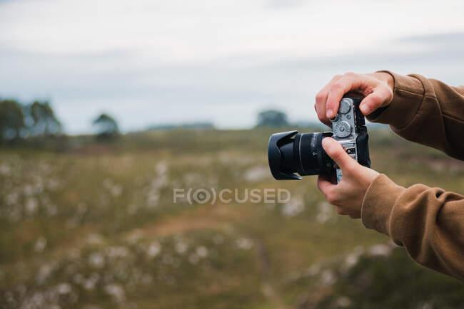 Crop anonimo fotografo maschio in giacca calda scattare foto sulla fotocamera professionale di vasto campo erboso il giorno coperto — Foto stock