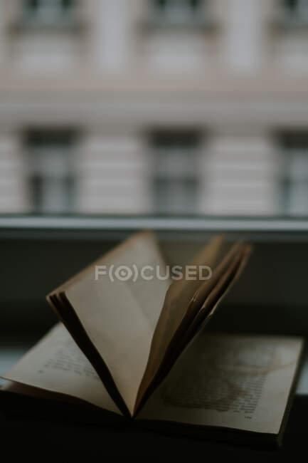 Учебник с кружками из кружки напитка на странице напротив окна и здания в вечернее время — стоковое фото