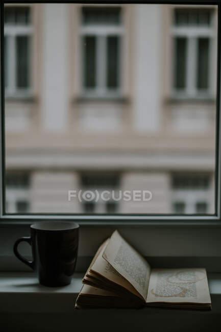 Учебник с кружками из напитков на странице возле кружки к окну и здания вечером — стоковое фото