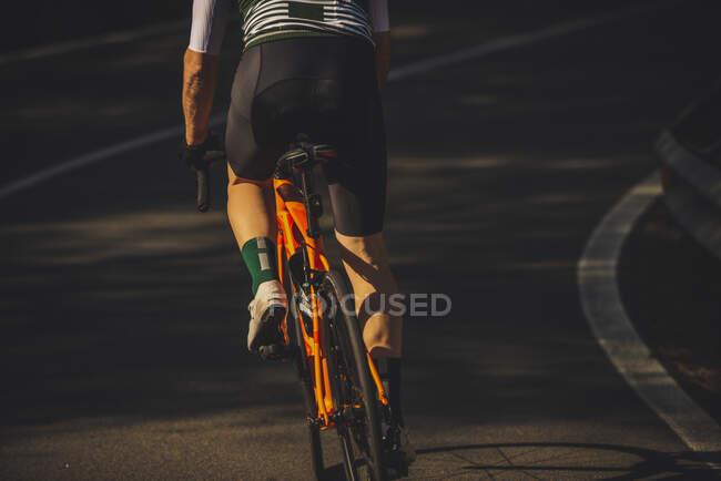 У сонячному дні молодий спортсмен на асфальтній дорозі їде велосипедом серед буйних зелених дерев. — стокове фото