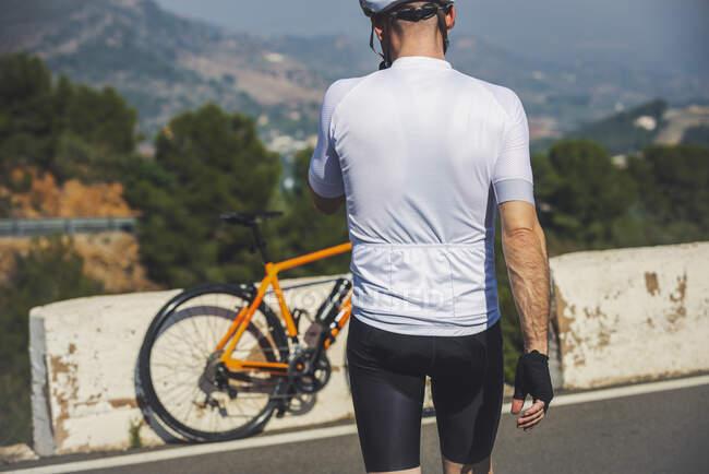 Вид сзади на неузнаваемого молодого велосипедиста в защитном шлеме и спортивной одежде, идущего рядом с велосипедом, припаркованным на асфальтированной дороге против голубого неба — стоковое фото