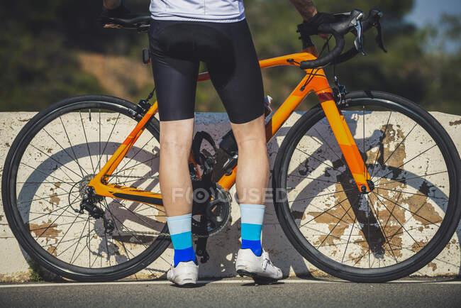 Невпізнаваний велогонщик у шортах і кросівках стоїть біля сучасного велосипеда на сонячній літній вулиці. — стокове фото