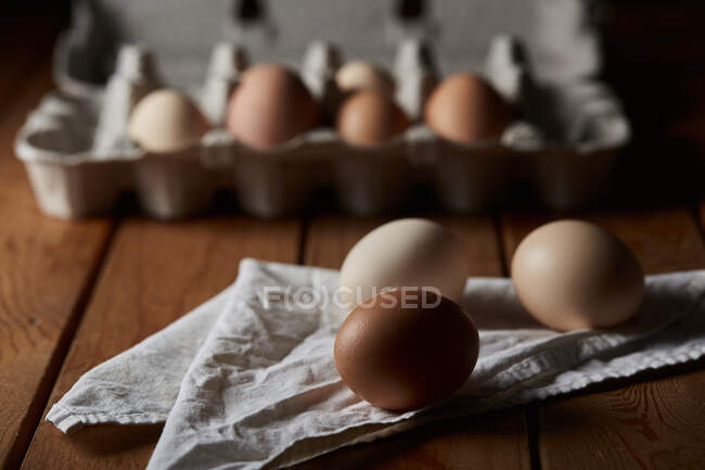 Uncooked eggs in container and on napkin placed on wooden table in kitchen for cooking breakfast — Stock Photo