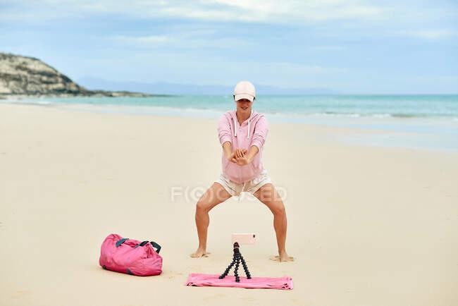 Полный набор веселых активных женских отрядов путешественниц во время тренировок на песчаном пляже и записи видео на мобильный телефон — стоковое фото