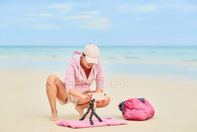 Full body of female travel blogger putting cellphone on tripod in sand for shooting video for social media — Stock Photo