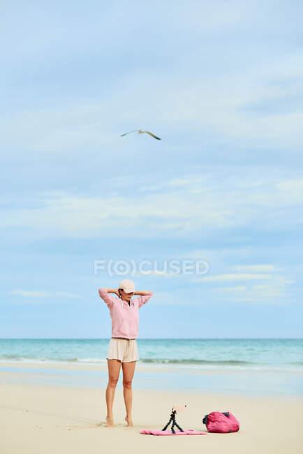 Тіло щасливих жінок-мандрівниць під час тренування на піщаному пляжі і запису відео на мобільному телефоні — стокове фото